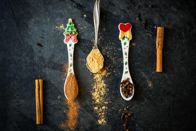 Gewürze für weihnachtslebkuchenplätzchen in den löffeln