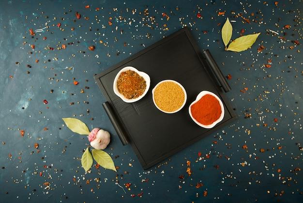 Gewürze im kasten auf einem dunkelen. helle gewürze teller, die auf einem holztablett mit griffen auf einem dunkelen texturiert stehen.