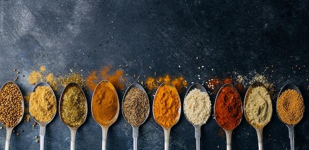 Gewürze im löffelhintergrund. sorten von gewürzen (kurkuma, pfeffer, chili, koriander, zimt) und paprika zum kochen. kulinarisches lebensmittelkonzept.