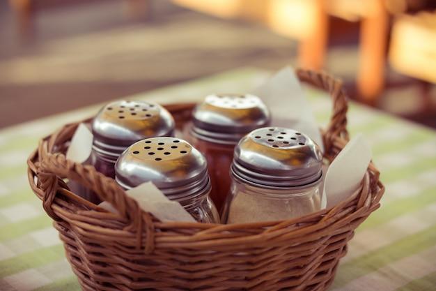Gewürze in glasflaschen in einem weidenkorb auf dem tisch im café. mittagessen an einem sommertag im freien