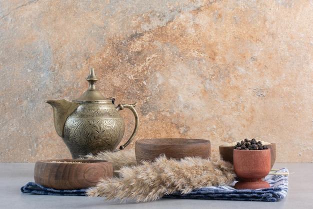 Gewürze in rustikalen holzschalen mit einer teekanne beiseite.