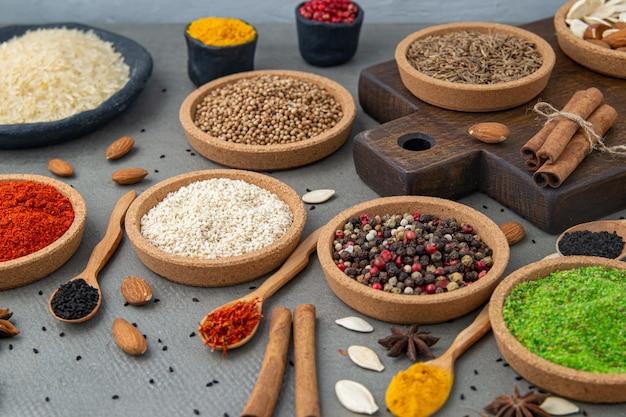 Gewürze liegen in den schüsseln und in den hölzernen löffeln, draufsicht, weichzeichnung. gewürze und gewürze für das kochen in der zusammensetzung auf dem tisch.
