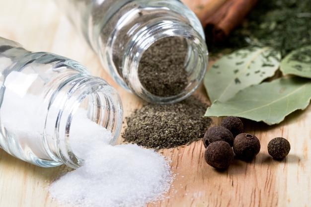 Gewürze: pfeffer, salz, lorbeerblätter, zimt und kräuternahaufnahme auf hölzernem hintergrund