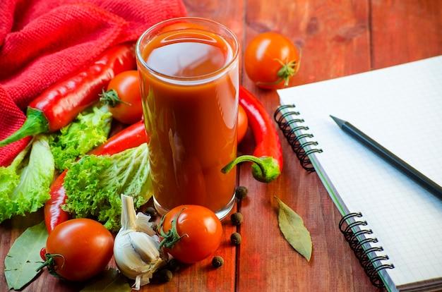 Gewürze, saft, gemüse und ein notizbuch zum schreiben von rezepten