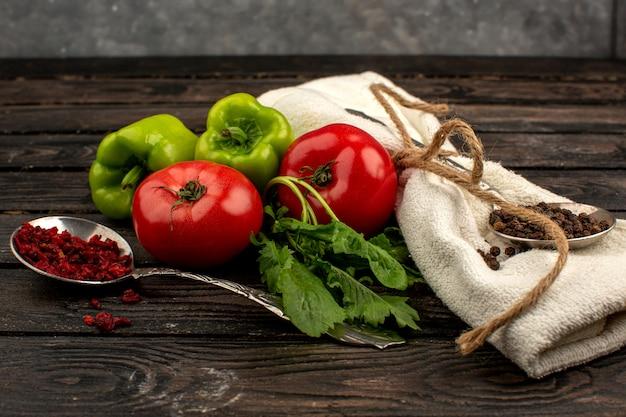 Gewürze und gemüse rote reife frische tomaten und grüne paprika zusammen mit cremefarbenen handtuch auf einem rustikalen holzboden