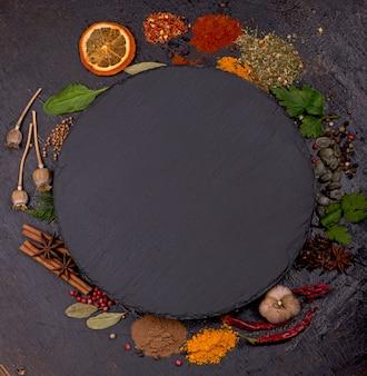 Gewürze und gewürze zum kochen auf schwarzem grund.