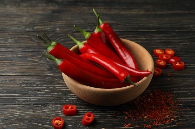 Gewürze und schüssel mit chili-pfeffer auf holzwand