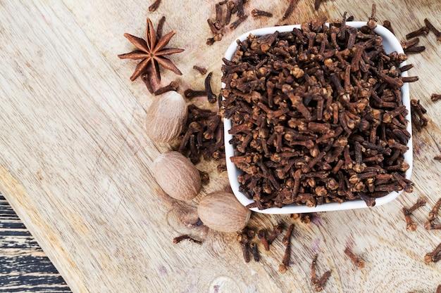 Gewürze von nelken, die auf einem alten holztisch in der küche verstreut sind, duftende gewürze von nelken werden beim kochen während der zubereitung von fleisch und anderen gerichten und konserven verwendet