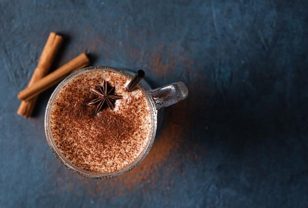 Gewürzen sie kaffee latte mit zimt und schokolade auf dem dunkelblauen tisch. draufsicht