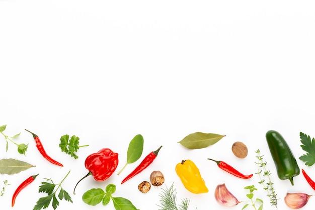 Gewürzkräuterblätter und -pfeffer auf weißem hintergrund. gemüse-muster. blumen und gemüse auf weißem hintergrund. ansicht von oben, flach.