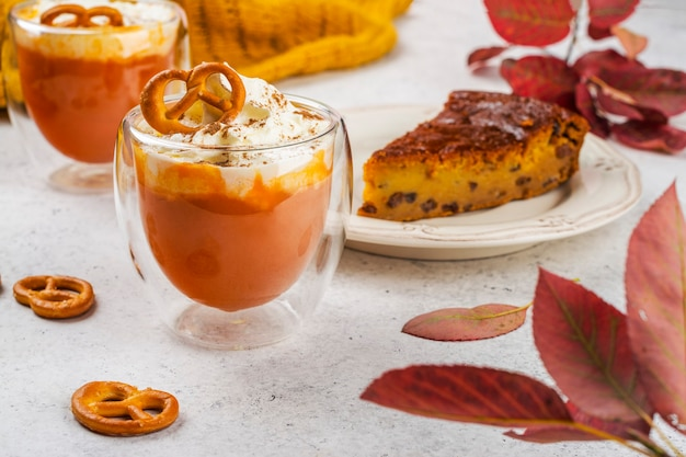 Gewürzkürbiskuchen-orangen-latte-getränk mit zimt-, sahne- und brezelkeks.