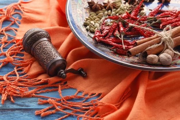Gewürzmühle und verschiedene aromatische kräuter auf teller