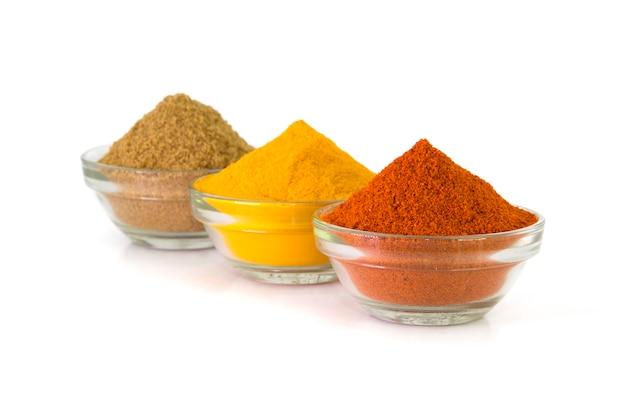 Gewürzpulver: chili, kurkuma & koriander in schüssel isoliert auf weißer oberfläche