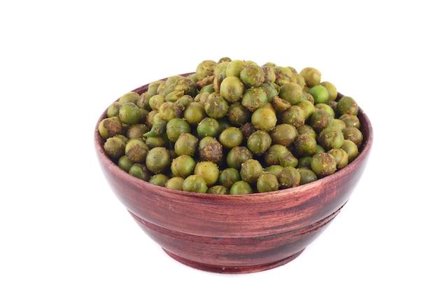 Gewürzte gebratene grüne erbsen {chatpata matar} indischer snack. getrocknete gesalzene grüne erbsen in der holzschale mit löffel auf weißem hintergrund