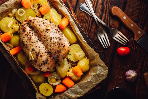 Gewürzte hühnerbrust im ofen mit gemüse auf backblech gebacken