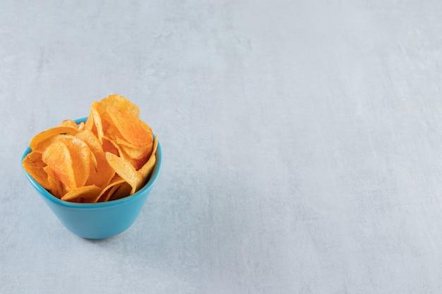 Gewürzte knusprige chips in blauer schüssel auf stein.