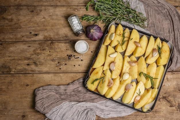 Gewürzte rohe kartoffelstücke zum backen vorbereitet.