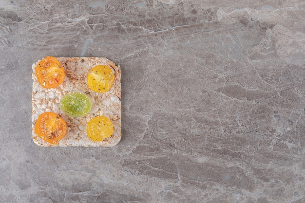Gewürzte tomatenscheiben mit reiskuchen darunter auf der marmoroberfläche