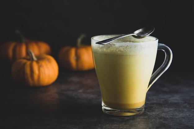 Gewürzter goldener milchkürbisherbst latte-getränkmilchshake mit sahneschaum