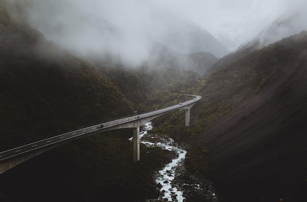 Gewundene autobahnbrücke im nebligen tal