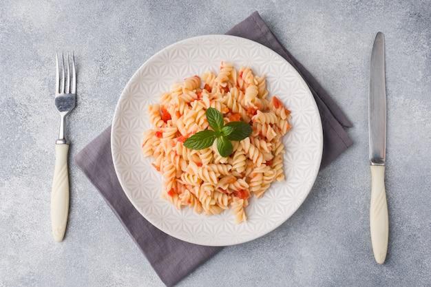 Gewundene teigwaren mischten mit kirschtomaten und tomatensauce auf einer platte.