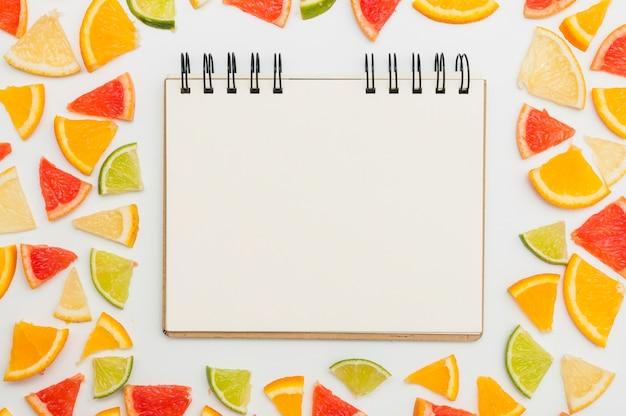 Gewundener leerer notizblock umgeben mit dreieckigen scheiben der zitrusfrucht auf weißem hintergrund