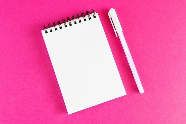 Gewundener notizblock auf hellem rosa