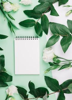 Gewundener notizblock eustoma blüht und verlässt auf doppeltem grünem und weißem hintergrund