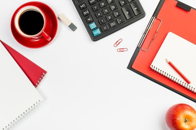 Gewundener notizblock, kaffeetasse, radiergummi, taschenrechner, gewundener notizblock auf klemmbrett mit rotem ganzem apfel auf weißem hintergrund