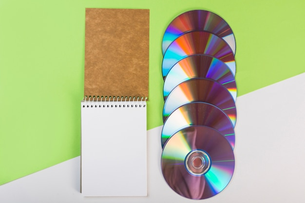 Gewundener notizblock mit bunten digitalschallplatten auf grünem und weißem doppelhintergrund