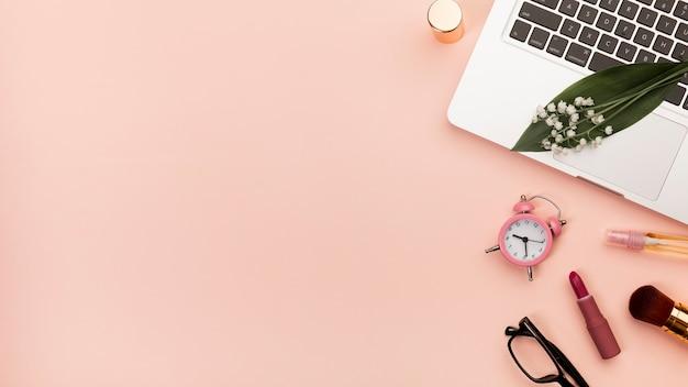 Gewundener notizblock mit lippenstift, wecker, brillen auf laptop gegen pfirsichhintergrund