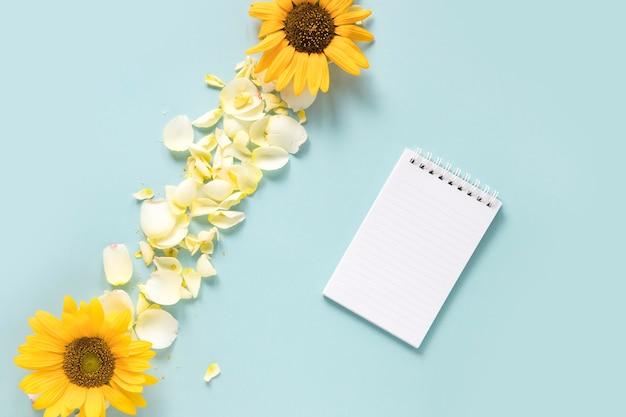 Gewundener notizblock nahe sonnenblumen und blumenblättern auf blauem hintergrund