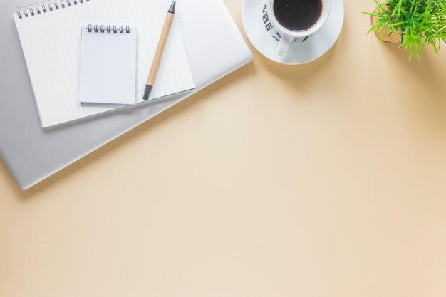 Gewundener notizblock und stift auf laptop mit kaffeetasse auf beige hintergrund