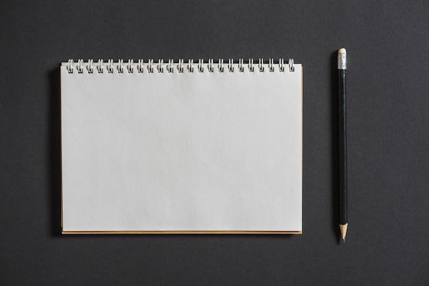 Gewundenes notizbuch mit bleistift auf grauem hintergrund