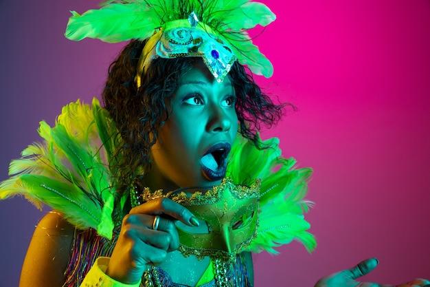 Gewundert. schöne junge frau im karneval, stilvolles maskeradekostüm mit federn, die auf steigungshintergrund in neon tanzen. konzept der feiertagsfeier, festliche zeit, tanz, party, spaß haben.