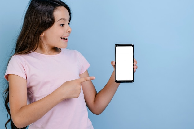 Gewundertes mädchen, das einen smartphone hält und auf den schirm schaut in ihm zeigt