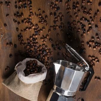 Geysirkaffeemaschine und sack mit zerstreuten bohnen