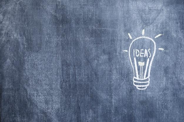 Gezogene beleuchtete glühlampe der idee gezeichnet mit kreide auf tafel