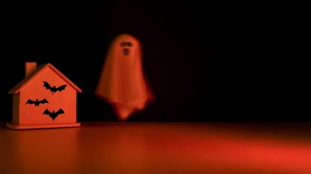 Ghost fliegt mit fledermäusen mit kopierraum durch das haus. halloween-urlaub.