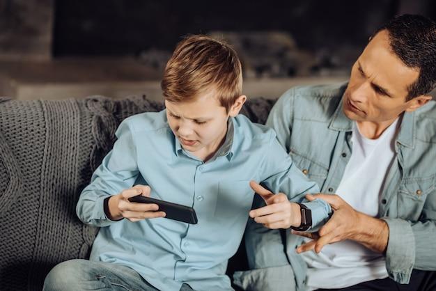 Gib es mir. der verärgerte junge vater, der versucht, das telefon seiner söhne wegzunehmen, möchte, dass er aufhört zu spielen, während der junge nicht loslässt