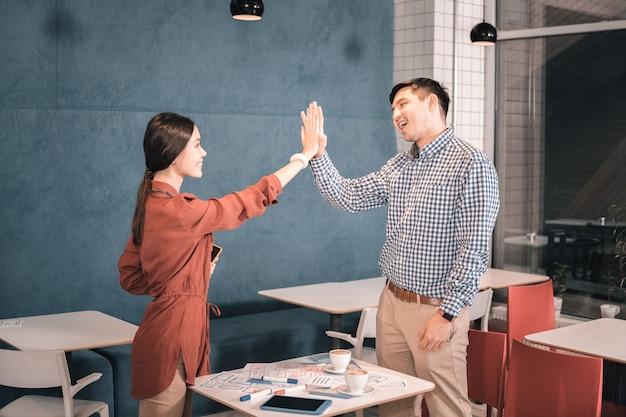 Gib mir fünf. ein paar freiberufler, die sich nach einem erfolgreichen arbeitstag gegenseitig high five geben