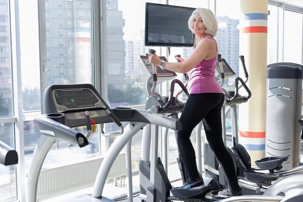 Gib nie auf. sportliche schöne ältere frau, die lächelt und auf übungsrad trainiert, während musik hört.