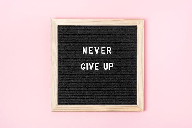 Gib niemals auf. motivationszitat auf schwarzem briefbrett auf rosa hintergrund. konzept inspirierendes zitat des tages. grußkarte, postkarte