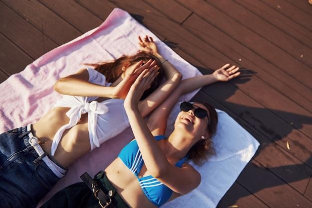 Gibt high five. draufsicht auf zwei mädchen am strand, die auf dem boden liegen und warmes sonnenlicht genießen.
