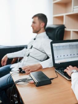 Gibt klare fragen. verdächtiger mann übergibt lügendetektor im büro. polygraphentest
