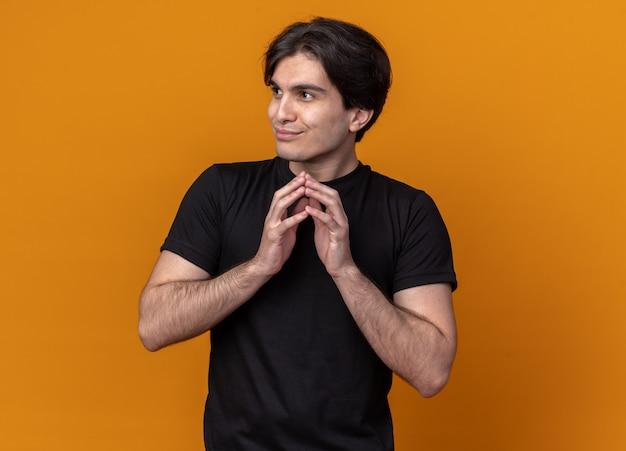 Gierig auf der seite junger gutaussehender kerl, der ein schwarzes t-shirt trägt und die hände zusammenhält, isoliert auf oranger wand?