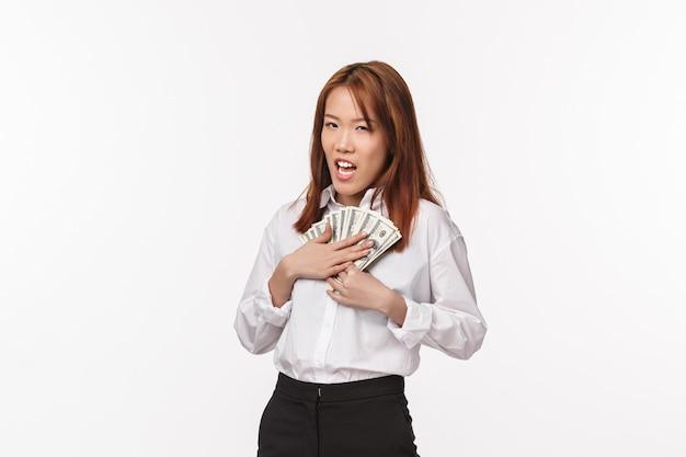 Gierige junge reiche asiatische frau im weißen hemd, geld auf die brust drücken und misstrauisch blinzeln, intrigen, bargeld gestohlen, für zukünftige ferien gespart, weiße wand bedürftig stehen