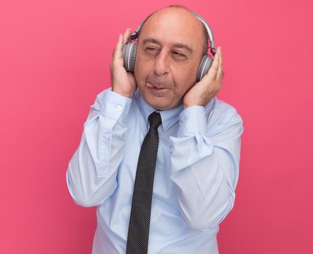 Gieriger blick auf einen mann mittleren alters, der ein weißes t-shirt mit krawatte und kopfhörern trägt, isoliert auf rosa wand