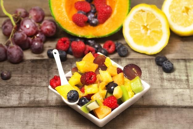 Gieriger fruchtsalat mit roten früchten auf holz