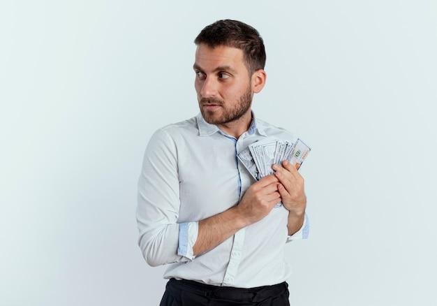 Gieriger gutaussehender mann hält geld, das die seite lokalisiert auf weißer wand betrachtet